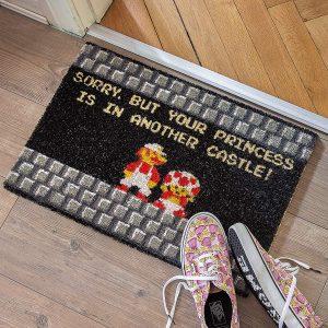 """Este felpudo muestra una escena icónica del clásico juego para ordenador que incluye la legendaria frase """"Sorry, but your princess is in another castle"""".Felpudo de fibra de coco de alta calidad con gran efecto de limpieza.Tamaño (B x H x T): 60 x 2 x 40 cm.Parte trasera de PVC antideslizante"""